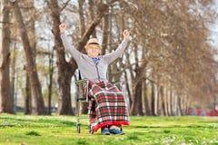 Älterer Herr, der Glück im Park gestikuliert Stockfotografie