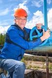 Älterer kaukasischer Mann in einer Arbeitsuniform mit Rohrventil Lizenzfreie Stockbilder