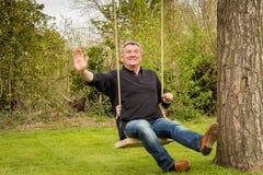 Älterer Mann auf einem Baumschwingen im Garten Lizenzfreies Stockbild