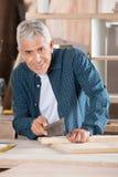 Älterer Mann-Ausschnitt-Holz mit sah in der Werkstatt Stockfotografie