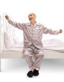 Älterer Mann in den auf einem Bett sitzenden und gähnenden Pyjamas Stockfotografie