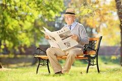 Älterer Mann, der auf einer Bank sitzt und eine Zeitung im Herbst liest Stockbilder