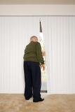 Älterer Mann, der aus Vorhängen heraus schaut Lizenzfreies Stockbild
