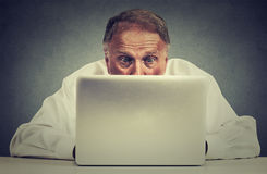 Älterer Mann, der bei Tisch das Arbeiten auf Laptop-Computer sitzt Stockbild