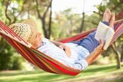 Älterer Mann, der in der Hängematte mit Buch sich entspannt Stockfotos