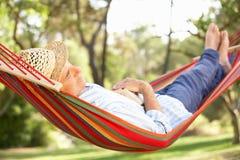 Älterer Mann, der in der Hängematte sich entspannt Lizenzfreie Stockfotografie