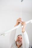 Älterer Mann, der eine Deckenleuchte installiert Stockbilder