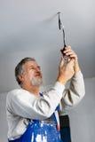 Älterer Mann, der eine Deckenleuchte installiert Stockfotografie
