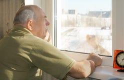 Älterer Mann, der an einem Fenster in Erinnerungen ergehend steht Lizenzfreie Stockfotografie