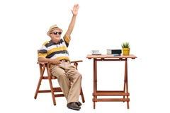 Älterer Mann, der an einem Tisch sitzt und mit der Hand wellenartig bewegt Lizenzfreie Stockfotografie