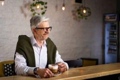 ?lterer Mann, der einen Kaffee in der Bar trinkt lizenzfreie stockfotos