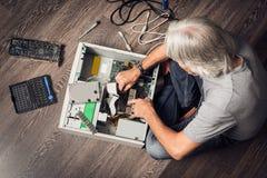 Älterer Mann, der einen Tischrechner zusammenbaut Lizenzfreies Stockbild