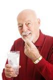 Älterer Mann, der Fisch-Öl-Kapsel nimmt Stockfotografie