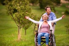 Älterer Mann, der Frau im Rollstuhl, grüne Herbstnatur drückt Lizenzfreies Stockbild