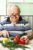 älterer Mann, der gesundes Lebensmittel zubereitet Lizenzfreies Stockfoto
