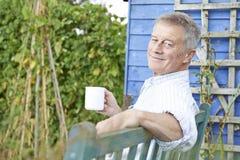 Älterer Mann, der im Garten mit Tasse Kaffee sich entspannt Stockfotos