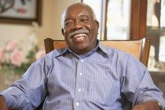 Älterer Mann, der im Lehnsessel sich entspannt Lizenzfreies Stockfoto