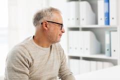 Älterer Mann, der im Ärztlichen Dienst sitzt Stockbilder