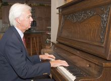 Älterer Mann, der Klavier spielt Stockbild