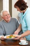 Älterer Mann, der Mahlzeit von Carer gedient wird Stockfoto