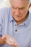 Älterer Mann, der Medizin betrachtet Stockfotografie