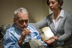 Älterer Mann, der Medizin mit Wasser nimmt Stockfotografie