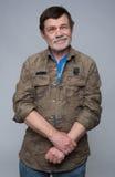 Älterer Mann, der mit den gekreuzten Armen steht Stockfotos
