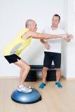 Älterer Mann, der mit persönlichem Trainer trainiert Stockfotos
