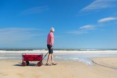 Älterer Mann, der mit Warenkorb am Strand geht Stockfotografie