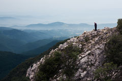 Älterer Mann, der am Rand der Klippe steht Stockbild