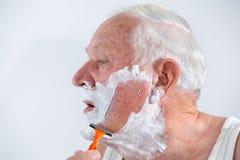 Älterer Mann, der seinen Bart rasiert Stockbilder