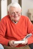 Älterer Mann, der sich zu Hause im Stuhl-Lesebuch entspannt Stockfotos