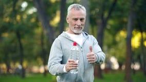 ?lterer Mann in der Sportkleidungsvertretungsflasche Wasser und Daumen oben, Aquabalance stockfoto