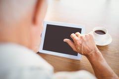Älterer Mann, der Tablette verwendet und Kaffee trinkt Stockbild