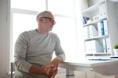 Älterer Mann, der am Tisch des Ärztlichen Diensts sitzt Stockbilder