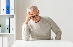 Älterer Mann, der am Tisch sitzt Lizenzfreie Stockfotos