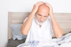 Älterer Mann, der unter Kopfschmerzen leidet Lizenzfreies Stockbild