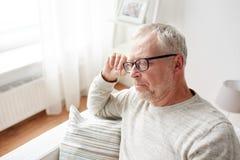 älterer Mann, der zu Hause auf Sofa und dem Denken sitzt Stockbild