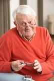 Älterer Mann, der zu Hause Blutzuckerspiegel überprüft Stockbild