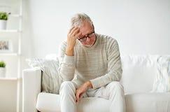 Älterer Mann, der zu Hause unter Kopfschmerzen leidet Stockbild