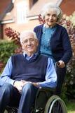 Älterer Mann im Rollstuhl, der von der Frau gedrückt wird Stockbilder