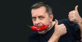 Älterer Mann mit rotem Pfeffer in seinem Mund Stockfoto
