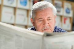 Älterer Mann mit Schnurrbartlesepapier in der Bibliothek Lizenzfreies Stockbild