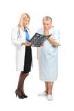 Älterer Mann mit seinem Doktor, der seinen CT betrachtet Stockfotografie