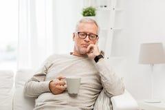 Älterer Mann mit Tasse Tee zu Hause Stockbild