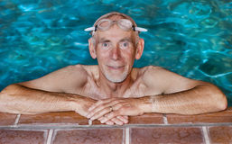 Älterer Mann am Rand des Swimmingpools Stockfoto