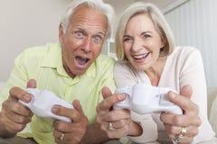 Älterer Mann-u. Frauen-Paare, die Videokonsolen-Spiel spielen Stockfotografie