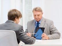 Älterer Mann und junger Mann mit Tabletten-PC Stockfoto