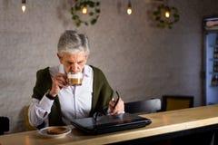 ?lterer Mann unter Verwendung des Laptops und des haben Kaffees in der Bar stockfotografie