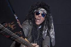 Älterer männlicher Gitarrist, der Gitarre über schwarzem Hintergrund bricht Lizenzfreies Stockfoto